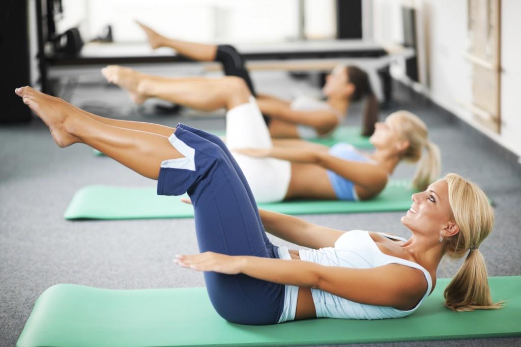 Group of women doing Pilates exercises.